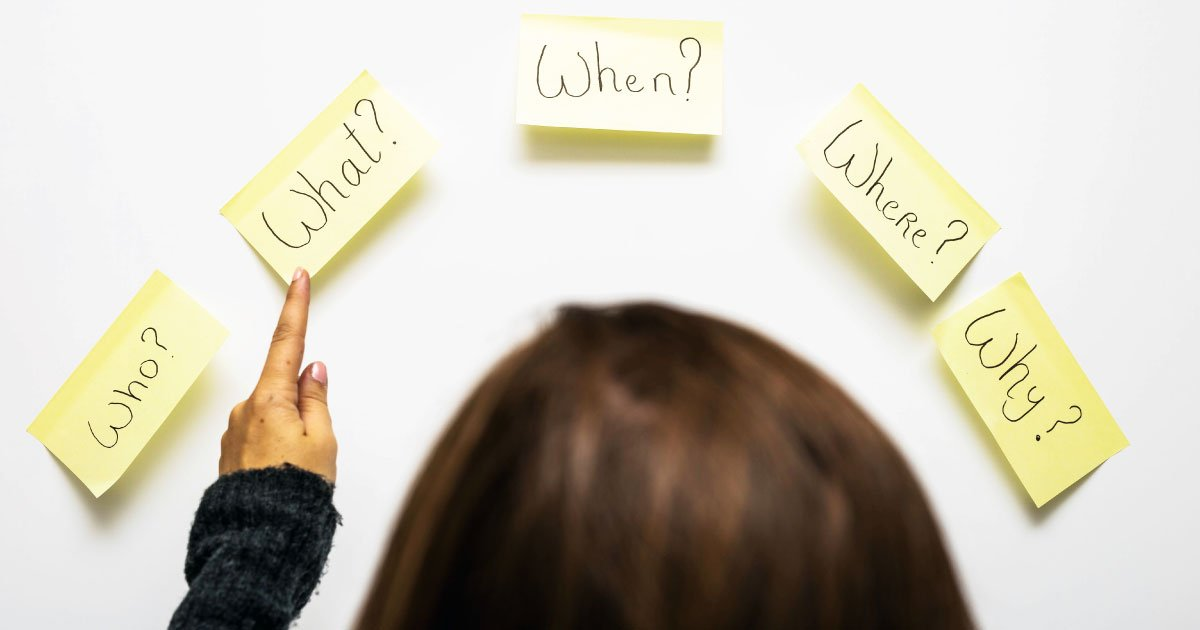 Woman looking at post it notes with who, what, when, where and why. Illustrates five questions women should ask their financial advisors.