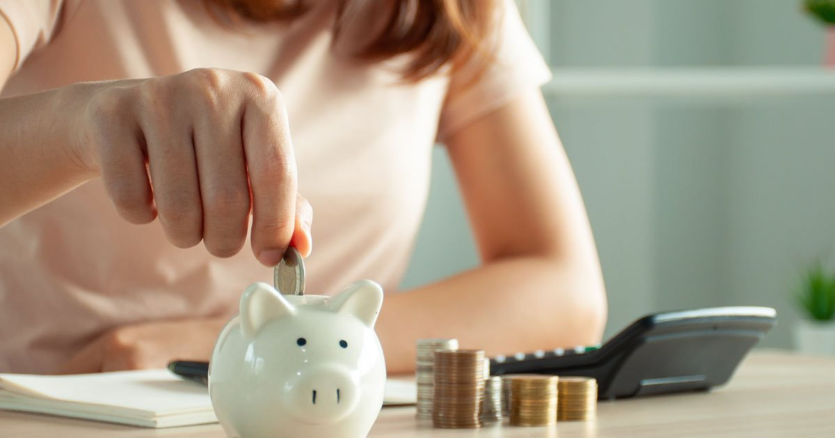 A woman planning for retirement by stacking coins near a piggy bank and making retirement planning calculations.