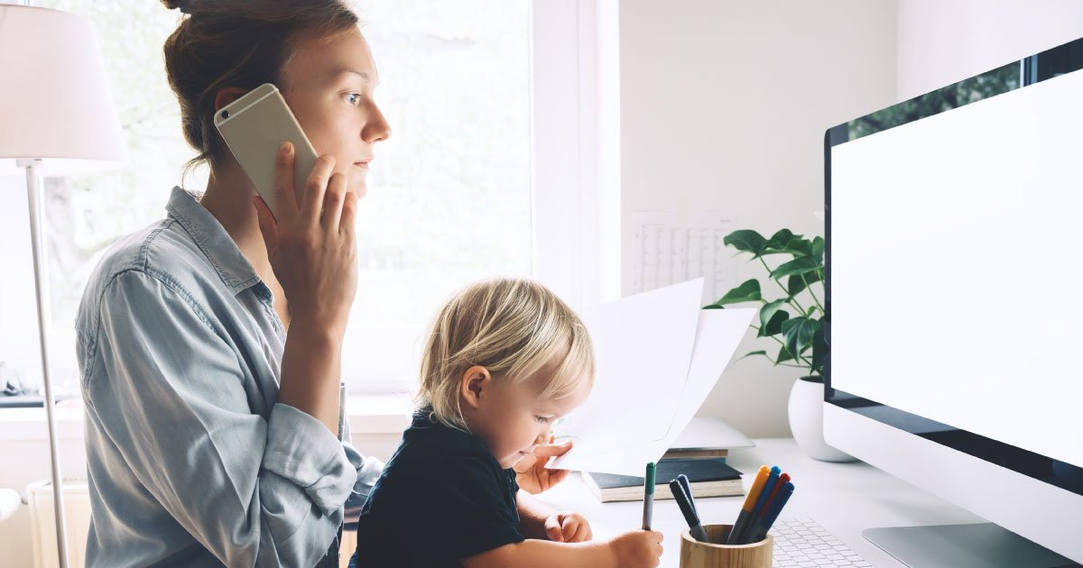 Woman working from home office during the pandemic with a child on her lap